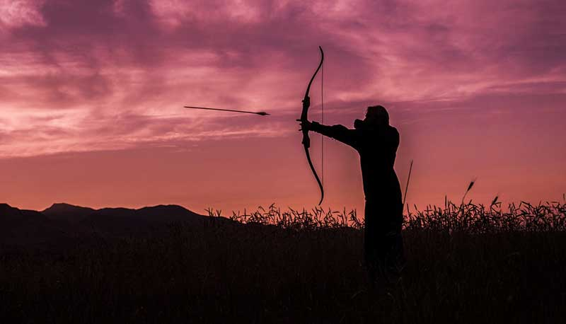 silhouette of man using a longbow
