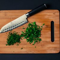 chopping board with a knife along with chopped vegetables