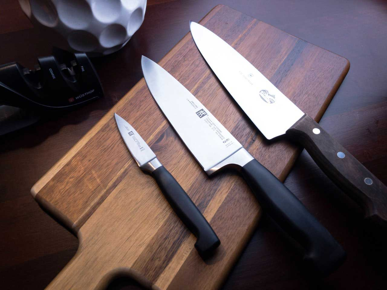 Three knifes on top of a chopping board